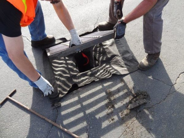 the storm grate being put back into place to hold the storm drain filter in place